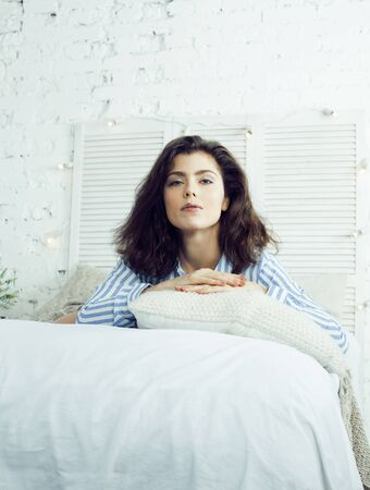 young pretty brunette woman in her bedroom sitting at window. lifestyle and people concept at home