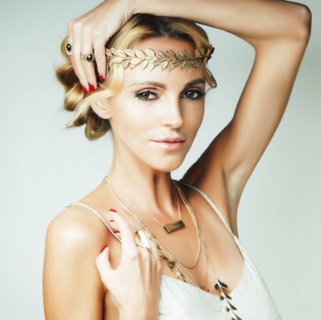 young blond woman dressed like ancient greek godess, gold jewelry and fashion makeup, people isolated on white background Banque d'images - 130014291