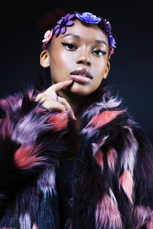 young pretty african american woman in spotted fur coat and flowers jewelry on black background close up