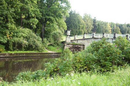 old vintage bridge on river in green park, landscape historical