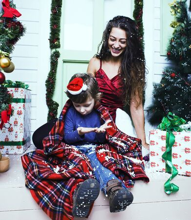 happy smiling family on Christmas at house with gifts, young mother and little son in Santas red hat, lifestyle holiday people concept