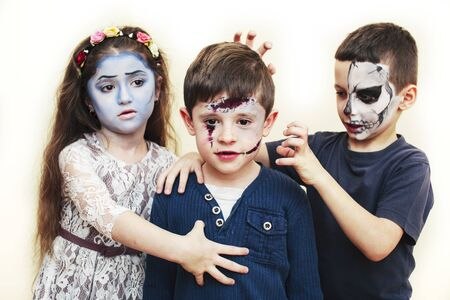 zombie apocalypse kids concept. Birthday party celebration facepaint on children dead bride, scar face, skeleton together having fun, halloween people