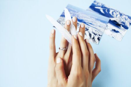 beautiful manicured woman hands with white feather on blue background closeup