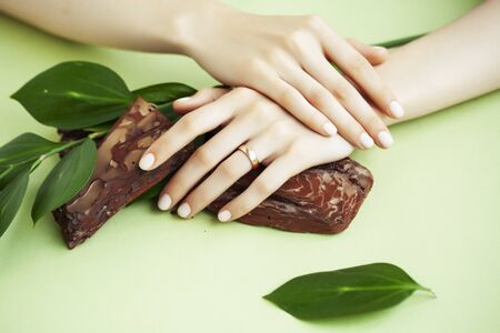 pretty perfect woman hands with white manicure and lgreen leaf on colorful background with wood, spa cosmetic concept closeup