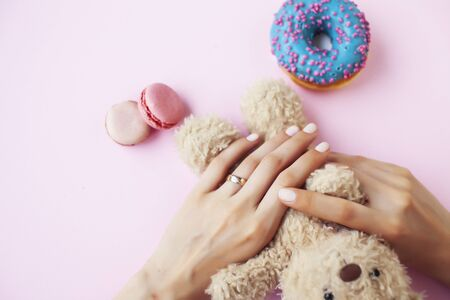 woman hands with manicure wearing wedding ring holdind teddy bear and macaroons on pink background closeup Stock Photo
