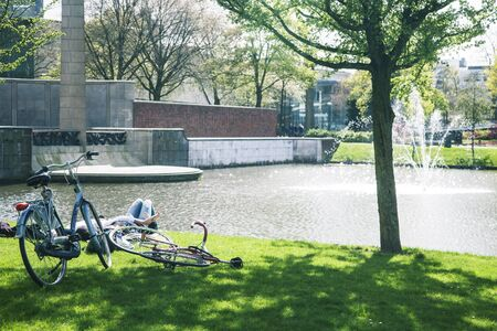 lifestyle people concept: couple of bicycle on green grass in summer park at fountain