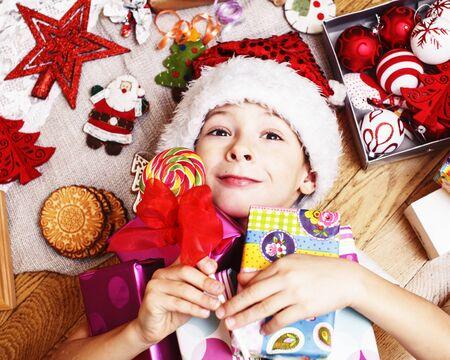 kleiner süßer Junge mit Weihnachtsgeschenken zu Hause. Nahaufnahme emotionales glückliches Lächeln im Chaos mit Spielzeug, Lifestyle-Urlaubskonzept für echte Menschen Standard-Bild