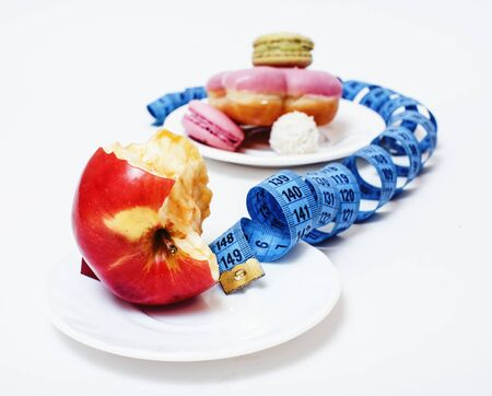 new real diet concept, question sign in shape of measurment tape between red apple and donut isolated on white Imagens