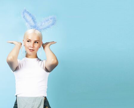 young pretty blond girl with rabbit ears posing cheerful on blue background, lifestyle people concept Stock Photo - 131521132