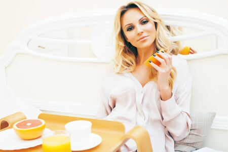 young beauty blond woman having breakfast in bed early sunny morning, princess house interior room, healthy lifestyle concept Stockfoto