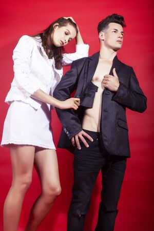young fashion style couple man and woman on red background, luxury stuff, lifestyle modern people sale concept