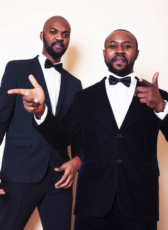 two afro-american businessmen in black suits emotional posing, gesturing, smiling. wearing bow-ties entertaiment stuff isolated on white background