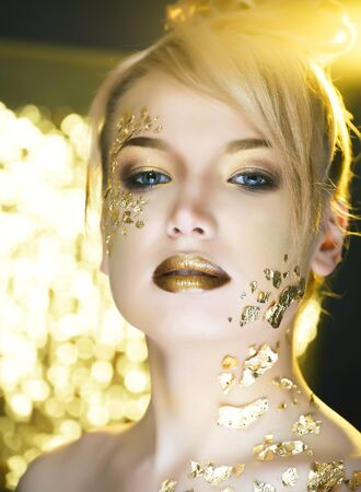 beauty blond woman with gold creative fashion make up, people at holiday concept