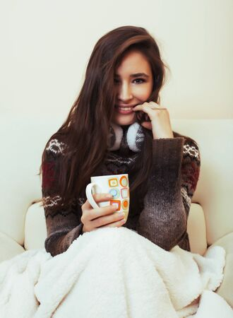 young pretty woman sitting in comfortable chair with coffee and blanket, winter season lifestyle people concept Stockfoto - 132025585