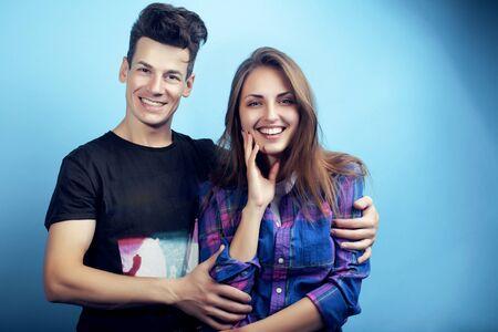 glückliches Paar zusammen posiert fröhlich auf blauem Hintergrund, Kerl und Studentinnen zusammen Freunde
