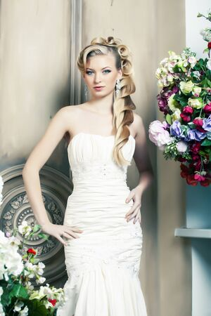 beauty young bride alone in luxury vintage interior with a lot of flowers, makeup and creative hairstyle Stock Photo