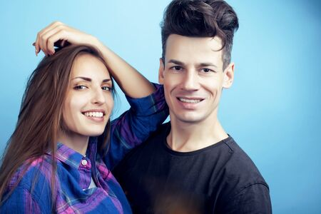 happy couple together posing cheerful on blue background , guy and girl students together friends Foto de archivo