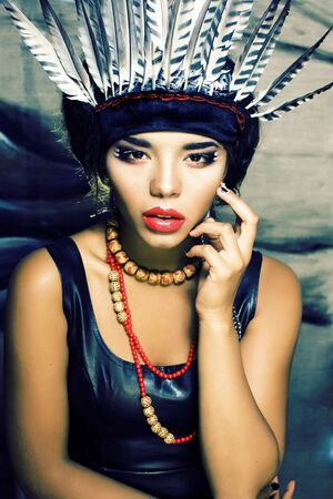 young pretty woman with make up like red indian, futher in hair, fashion hallowen concept Imagens - 132028509