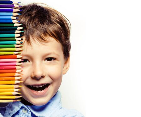 little cute boy with color pencils close up smiling, education face colored Фото со стока