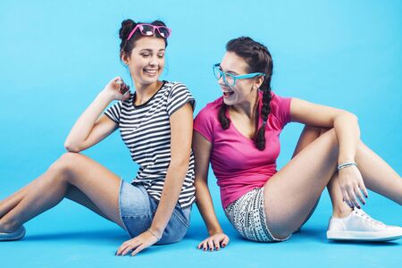 lifestyle people concept: two pretty young school teenage girls having fun happy smiling on blue background Imagens