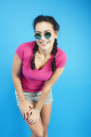 young pretty teenage modern hipster girl posing emotional happy on blue background, lifestyle people concept Imagens