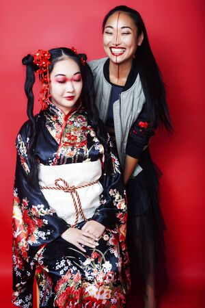 two pretty geisha girls friends: modern asian woman and traditional wearing kimono posing cheerful on red background