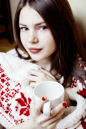 young pretty brunette woman in her bedroom sitting in christmas decorated blanket, happy smiling lifestyle people concept