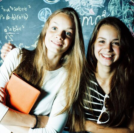 back to school after summer vacations, two teen girls in classroom with blackboard painted together