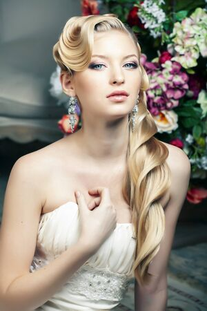 beauty young bride alone in luxury vintage interior with a lot of flowers, makeup and creative hairstyle Stok Fotoğraf