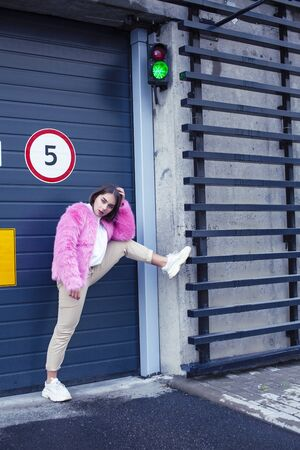 young cute girl teenager gesturing hanging around city parking and teasing with stop sign, lifestyle people concept Фото со стока