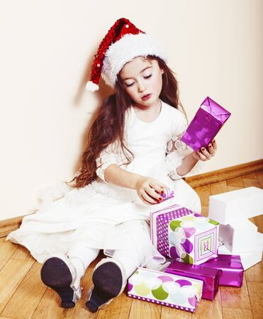 little cute girl in santas red hat waiting for Christmas gifts. holiday lifestyle people concept