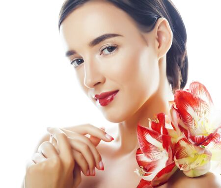young pretty brunette real woman with red flower amaryllis closeup isolated on white background. Fancy fashion makeup, bright lipstick, creative Ombre manicured nails