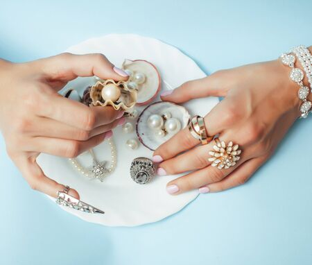 beautiful woman hands with pink manicure holding plate with pearls and sea shells, luxury jewelry concept Zdjęcie Seryjne