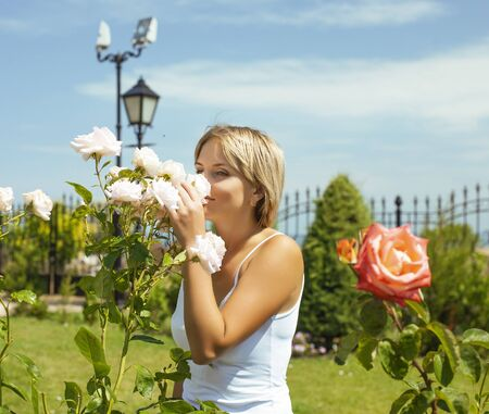 young pretty young woman in green rose garden happy smiling, lifestyle people concept
