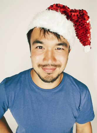 funy exotical asian Santa claus in new years red hat smiling 스톡 콘텐츠