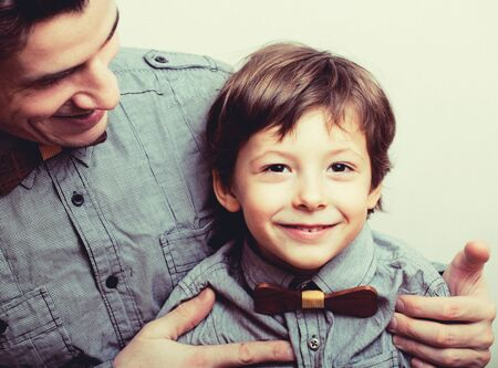 Vater mit Sohn in Schleifen auf weißem Hintergrund, lässiger Blick
