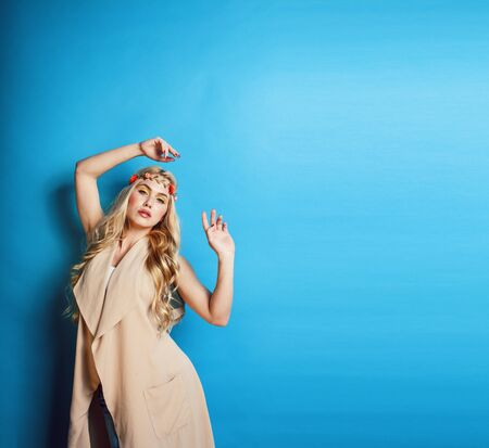 young blond woman dressed like ancient greek godess, jewelry close up isolated, beautiful girl hands manicured red nails on blue background copyspace