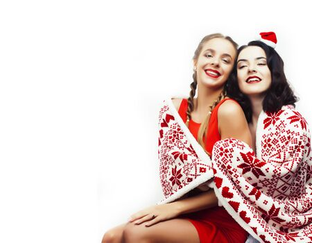 young pretty happy smiling blond and brunette woman girlfriends in Santas red hat and Christmas decorated blanket isolated on white background, holiday people concept