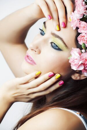young pretty brunette woman with pink flowers and manicure posing cheerful isolated on white background close up