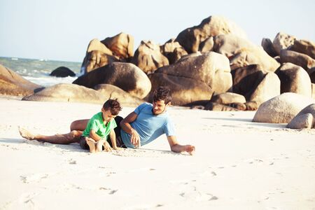 happy family on beach playing, father with son walking sea coast, rocks behind smiling taking vacation closeup