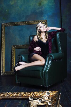 young blond woman wearing crown in fairy luxury interior with empty antique frames total wealth concept Banco de Imagens