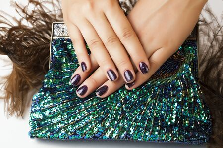 woman hands with shiny manicure holding little purse peacok feather, cosmetic and fashion people concept closeup Archivio Fotografico