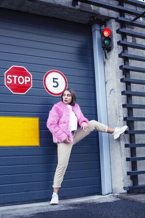 young cute girl teenager gesturing hanging around city parking and teasing with stop sign, lifestyle people concept