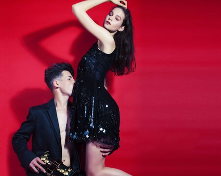 young fashion style couple man and woman on red background, lifestyle people concept