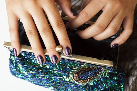 woman hands with shiny manicure holding little purse peacok feather, cosmetic and fashion people concept Archivio Fotografico