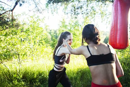 two diverse nations girls fighting boxing outside in green park, sport summer people concept