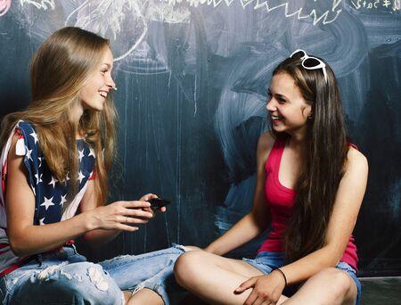 Nach den Sommerferien wieder in der Schule, zwei Teenager-Mädchen im Klassenzimmer mit zusammengemalter Tafel Standard-Bild
