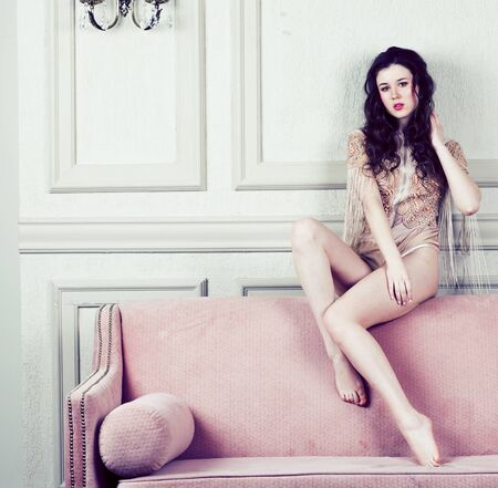 young pretty brunette girl in fashion dress on sofa posing in luxury rich home interior, lifestyle modern people concept