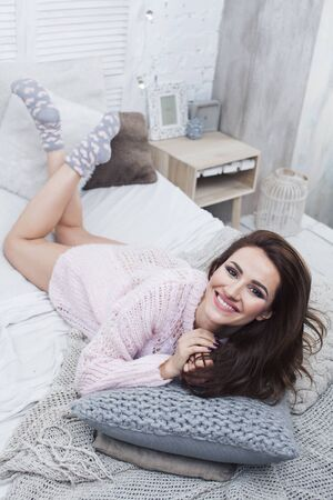 young pretty brunette woman in her bedroom sitting on bed with coffee. lifestyle people concept