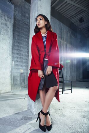 Junge hübsche afroamerikanische Frau in luxuriösem rotem Mantel, die modisch auf leerem Parkhaus posiert, Lifestyle-Konzept für reiche Leute
